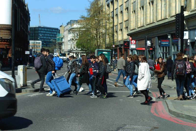 Люди пересекая crosswalk в коммерчески улице, Shoreditch, восточном Лондоне стоковое изображение rf