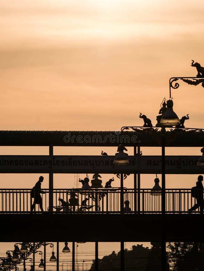 Люди пересекая Footbridge около статуи слонов & стоковые изображения rf