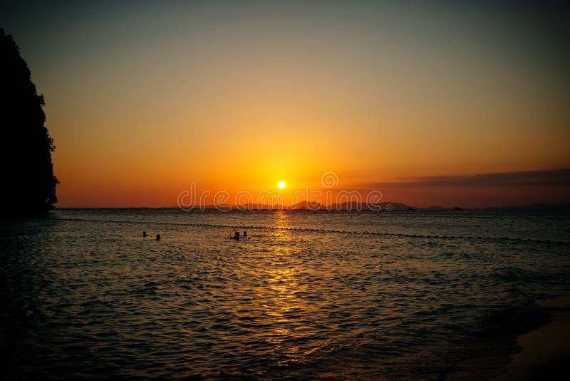 Люди плавают в море в вечере на заходе солнца стоковое фото