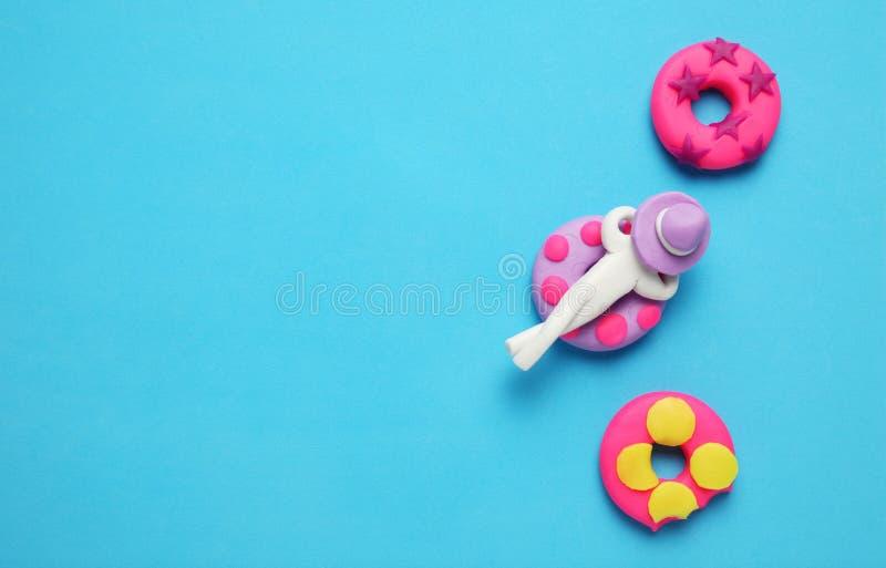 Люди пластилина ослабляя на раздувном lilo донута в бассейне Ослаблять и праздники лета мультфильма стоковые изображения