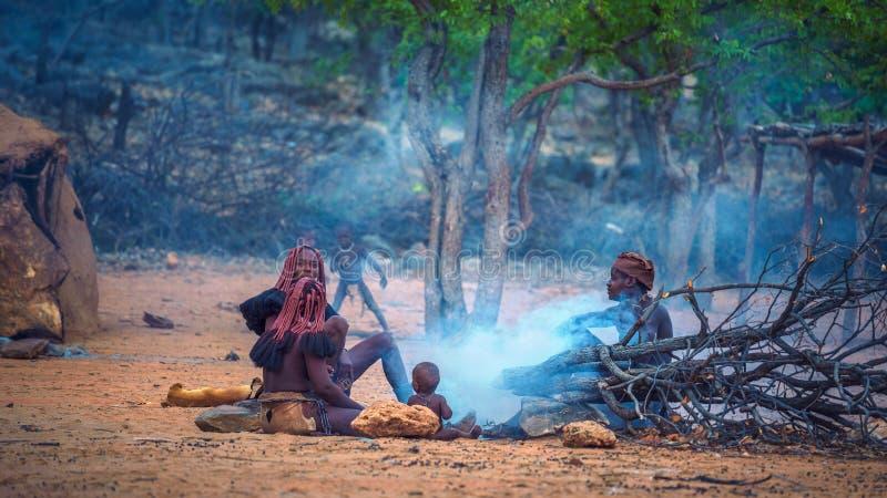 Люди племени Himba сидя вокруг огня в их деревне стоковая фотография
