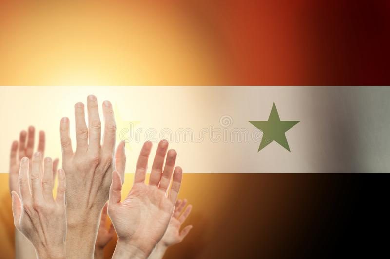 Люди поднимая руки и флаг Сирию на предпосылке Патриотическая концепция стоковое фото rf