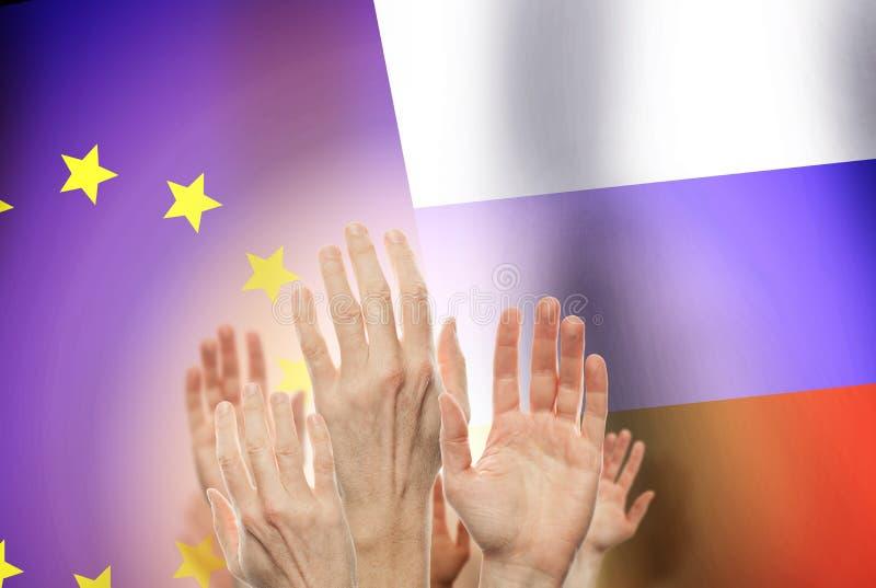 Люди поднимая руки на флаге России и предпосылке Европы соединения стоковая фотография
