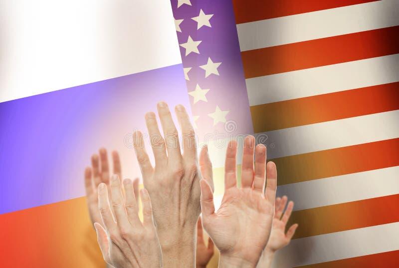 Люди поднимая руки на флаге России и предпосылке США стоковые фото