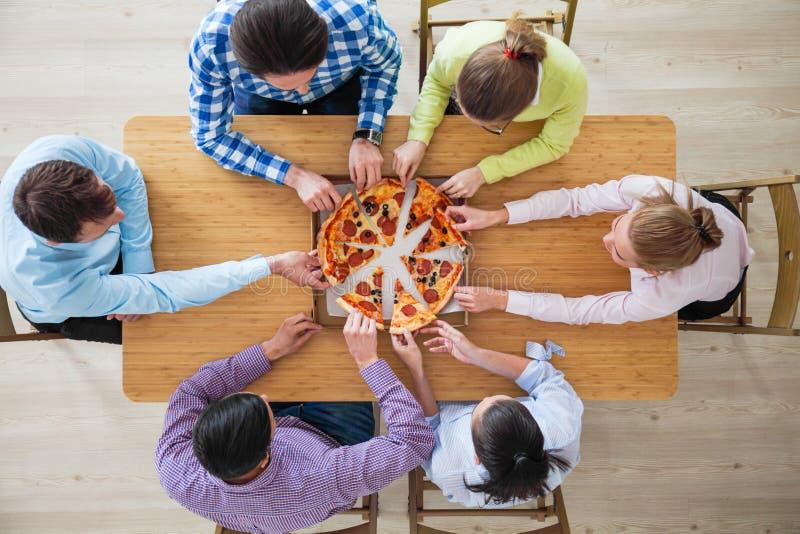 Люди принимая куски пиццы стоковые фото