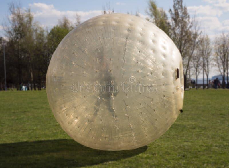 Люди свертывая вниз в гигантском шарике пузыря стоковое фото rf