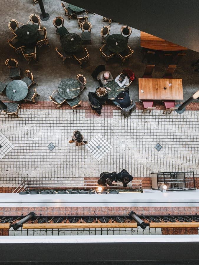 Люди сверху сидя на таблицах и идя быстро в мол города стоковая фотография rf