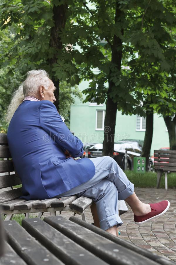 Люди сидя, модные одежды, скамейка в парке в современном cit стоковое фото