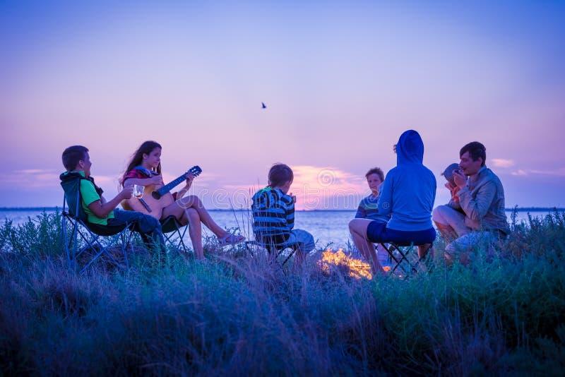 Люди сидя на пляже с лагерным костером на заходе солнца стоковая фотография rf