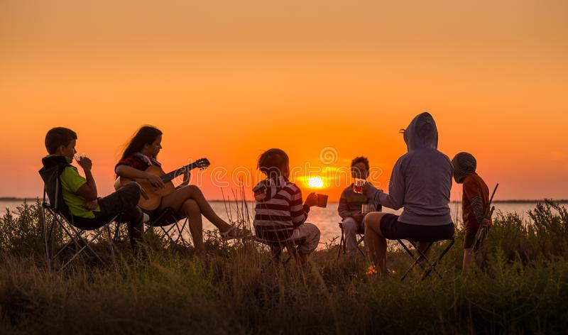 Люди сидя на пляже с лагерным костером на заходе солнца стоковое фото rf