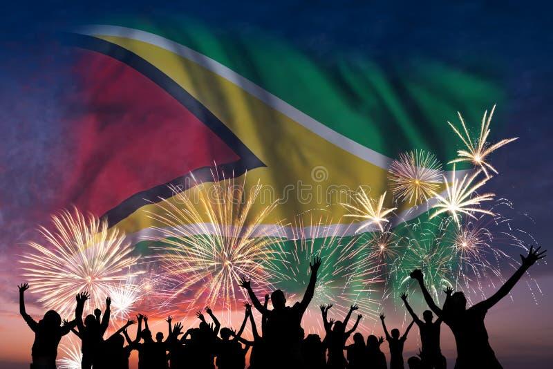 Люди смотрят на фейерверках и флаге Гайаны стоковые изображения