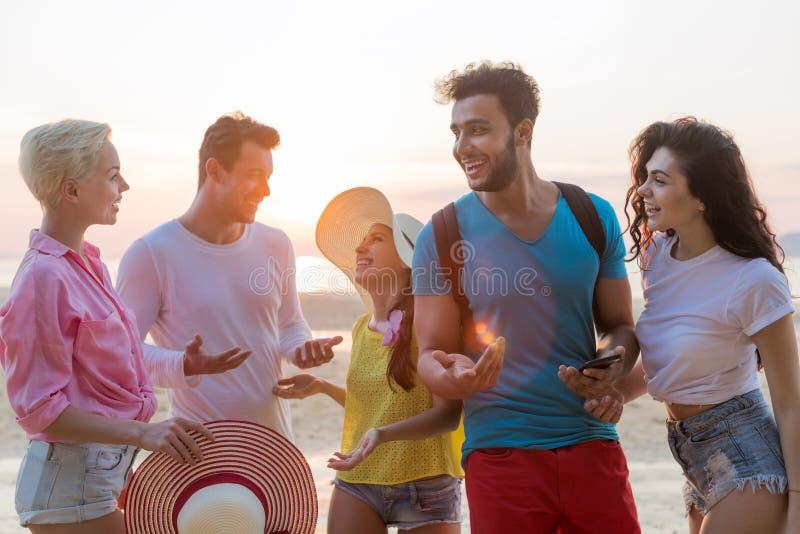 Люди собирают на пляж на заходе солнца говоря счастливый усмехаться, связь туристов гонки смешивания на взморье стоковое фото