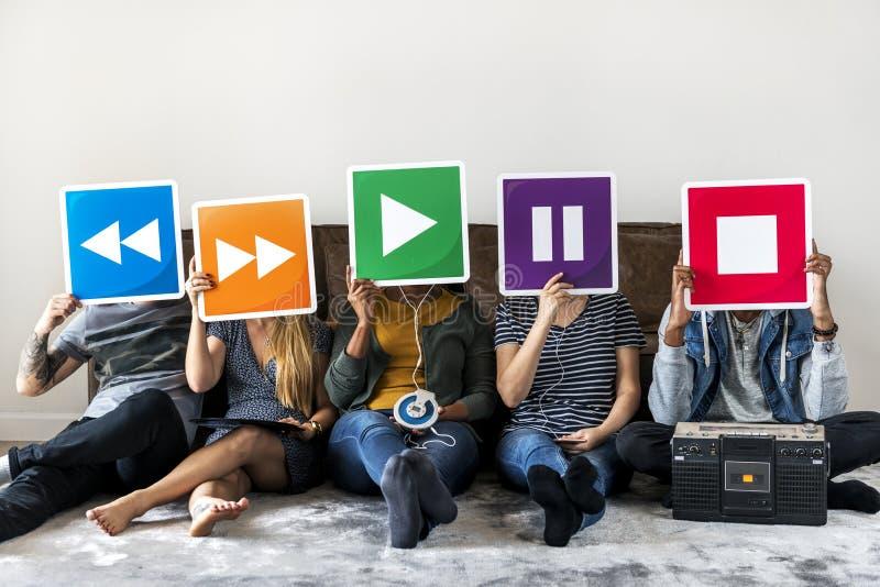 Люди совместно наслаждаясь музыкой держа значки стоковая фотография rf
