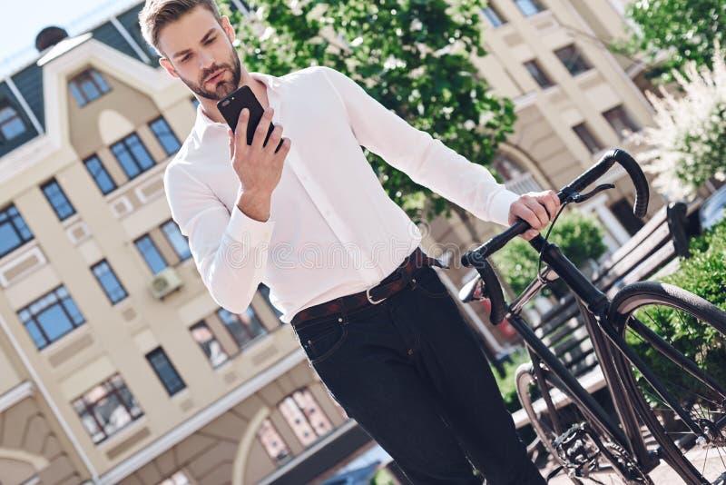 Люди, сообщение, технология, отдых и образ жизни - человек битника с smartphone на телефоне фиксированного велосипеда шестерни бе стоковое фото rf