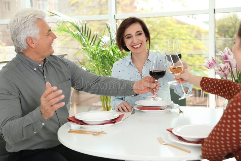 Люди со стеклами вина на таблице стоковое изображение rf
