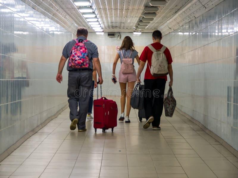 Люди с багажом идут через подземный переход стоковые фото