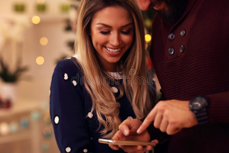 Люди с smartphone во время рождества дома стоковая фотография