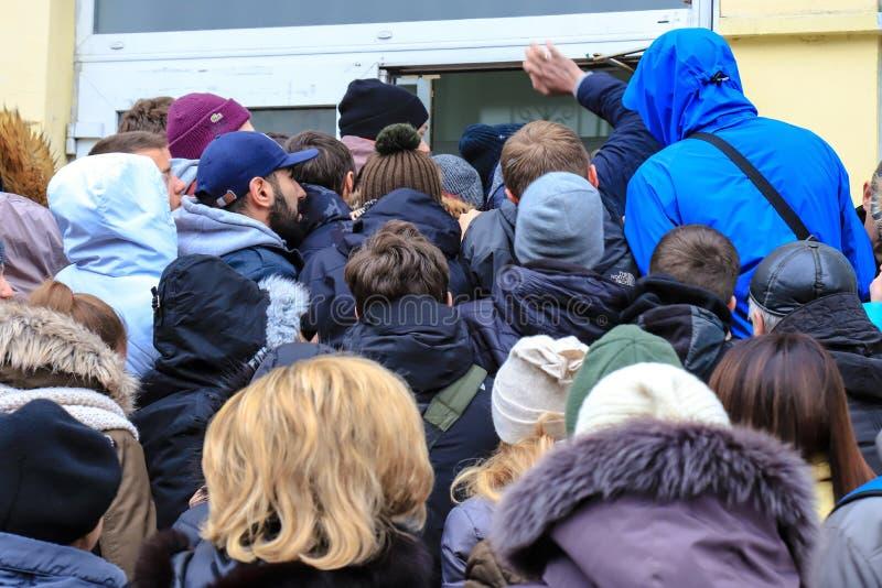 Люди толпятся около магазина во время продажи Покупатели входят торговый центр в черную пятницу стоковое фото