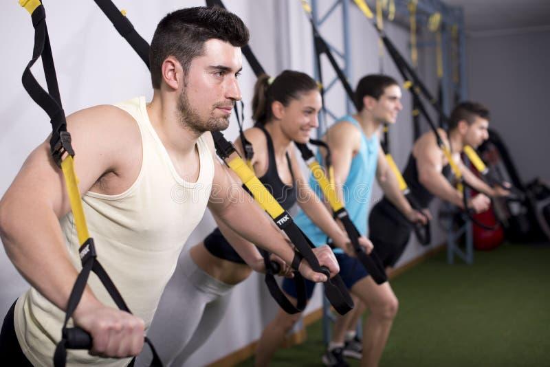 Люди тренируя в спортзале в тренировке подвеса стоковая фотография
