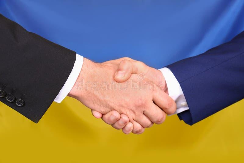 Люди тряся руки против украинского национального флага Международные отношения стоковые изображения