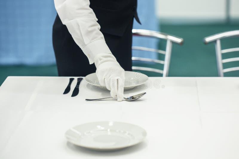 Люди устанавливая таблицу для обедающего на свадьбу стоковое изображение