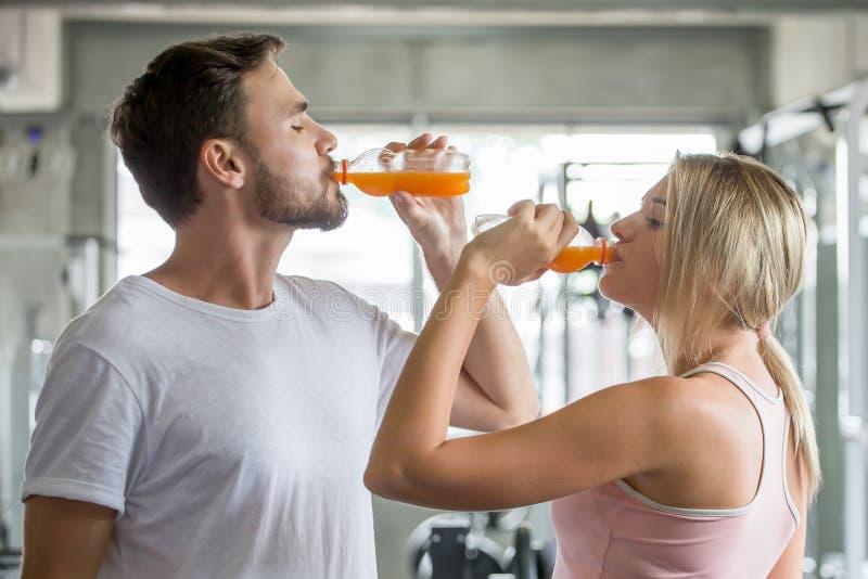 люди фитнеса пар молодые выпивая бутылки апельсинового сока в спортзале спорт человек и тренировки женщины стоковые изображения