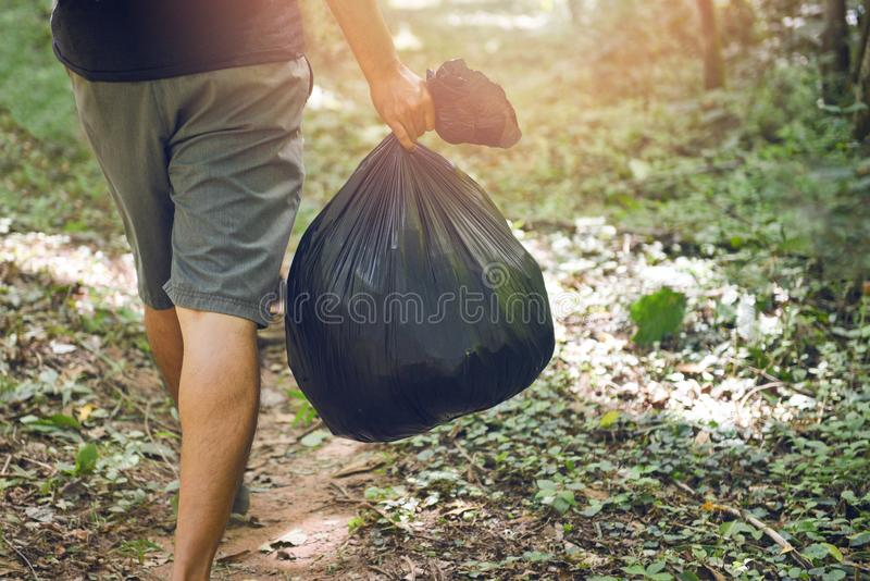 Люди экологичности сбора мусора очищая парк - руку человека держа черные пластиковые сумки отброса в лесе, очищать стоковые изображения
