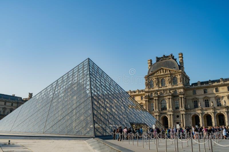 Люди queueing под пирамидой известного Лувр на Париже стоковое изображение