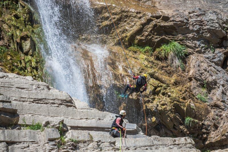 Люди rappelling во впечатляющем водопаде стоковые фотографии rf