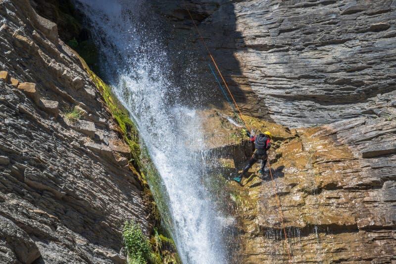 Люди rappelling во впечатляющем водопаде стоковые фото