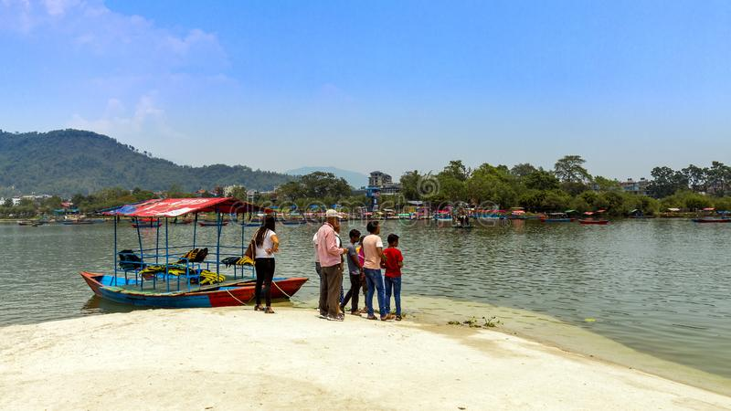 Люди Weiting для шлюпок в заливе Pokhara шлюпки виска Tal Barahi стоковая фотография rf