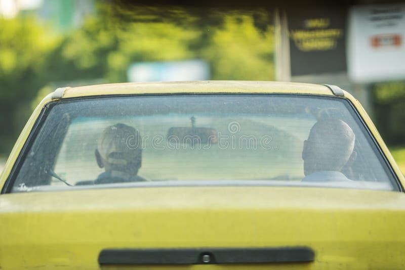 2 люд в старом желтом немецком такси автомобиля стоковые фото