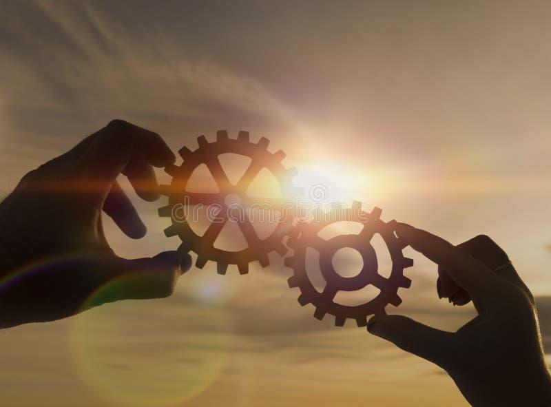 2 люд держат шестерни на заднем плане против захода солнца стоковое фото