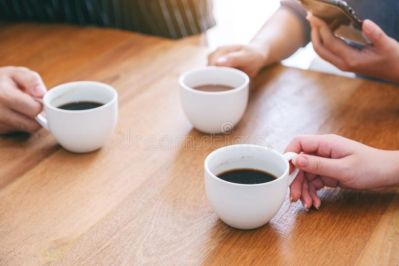 3 люд держа кофейные чашки для того чтобы выпить на деревянном столе стоковое изображение rf