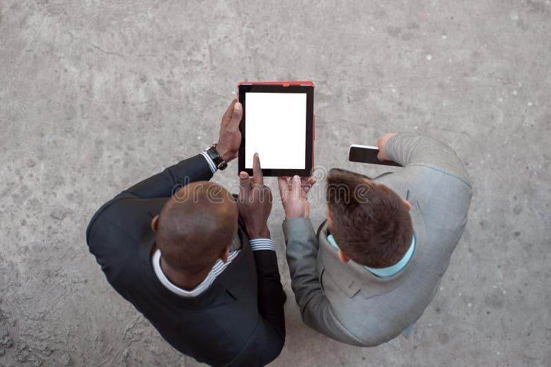 2 люд держа таблетку и обсуждают дело outdoors стоковые изображения