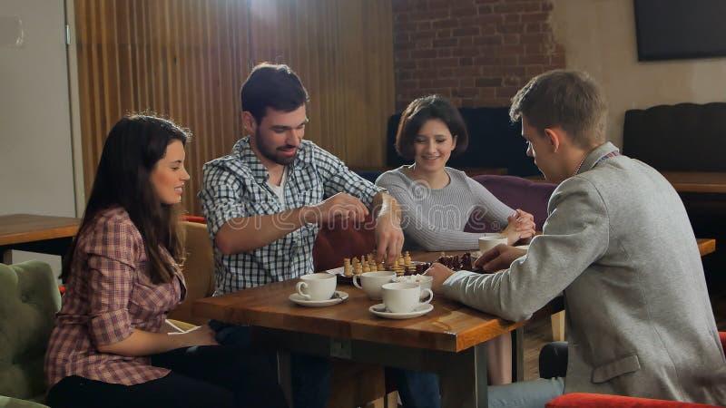 2 люд играя шахмат, наблюдать девушек стоковые фото