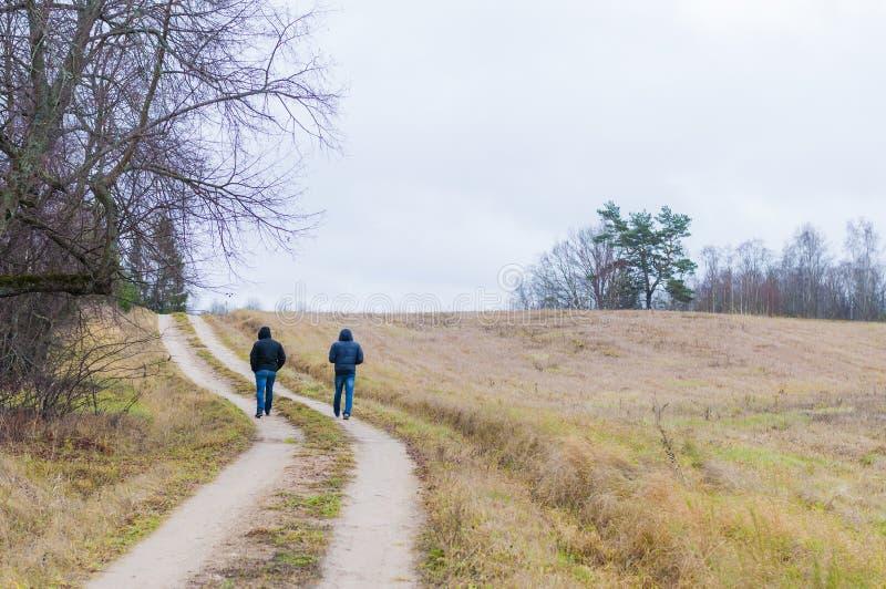 2 люд идя изогнутой сельской дорогой стоковые изображения