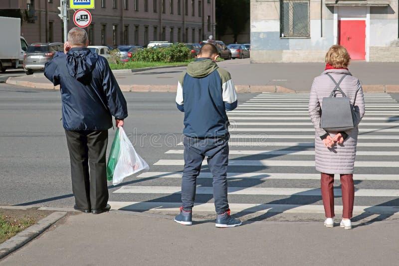 2 люд и женщина смотря на пешеходный переход стоковое изображение rf