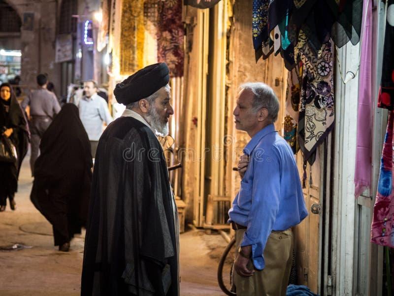 2 люд обсуждая в благотворительном базаре Isfahan, одном нося черном тюрбане, значащ он Sayyid, или Syed, выходец пророка Мухамме стоковые изображения