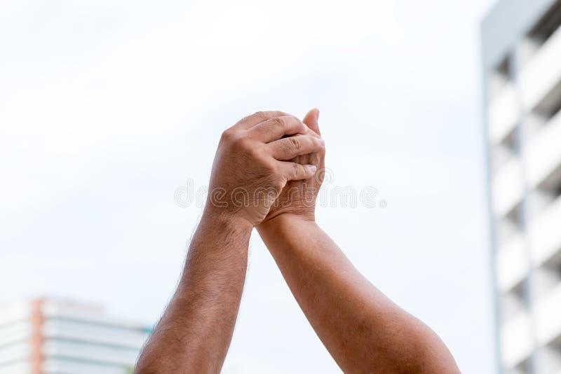 2 люд поднимают их руку для праздновать их успех стоковое фото rf