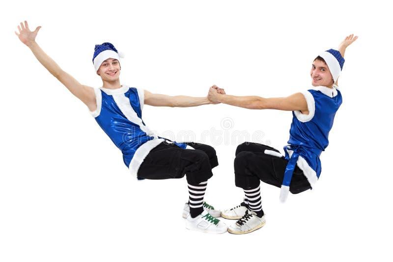 2 люд рождества в голубом santa одевают танцы против изолированной белизны внутри во всю длину стоковая фотография