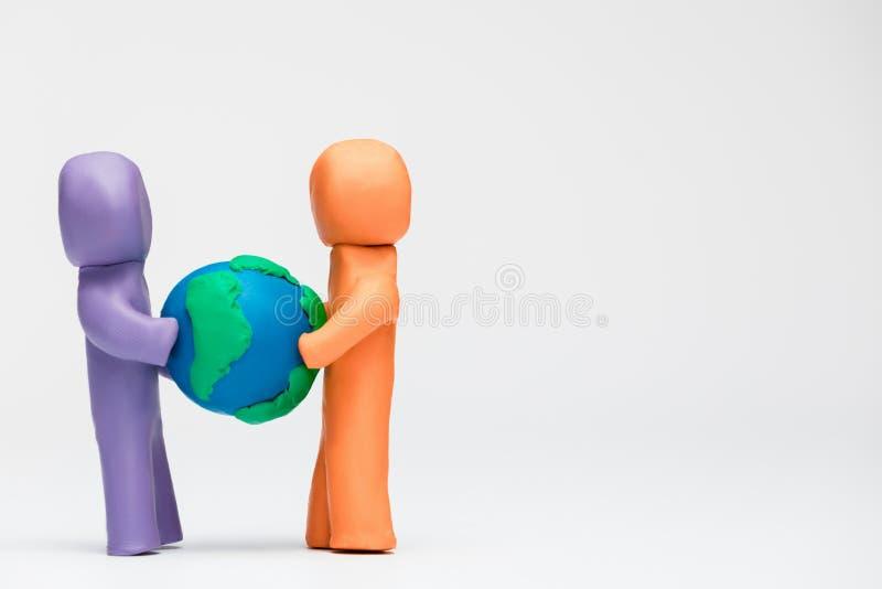 2 люд сделали из пластилина других цветов держа модель земли планеты стоковое изображение