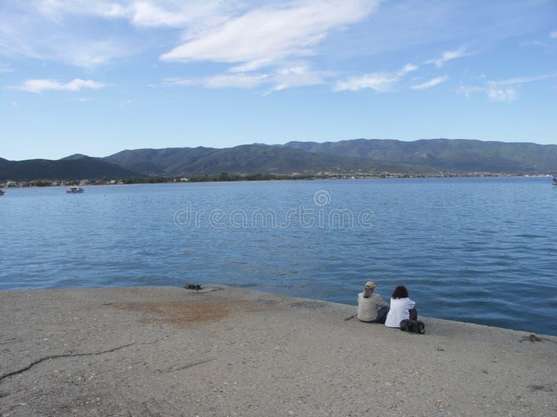 2 люд сидя на доке стоковое фото