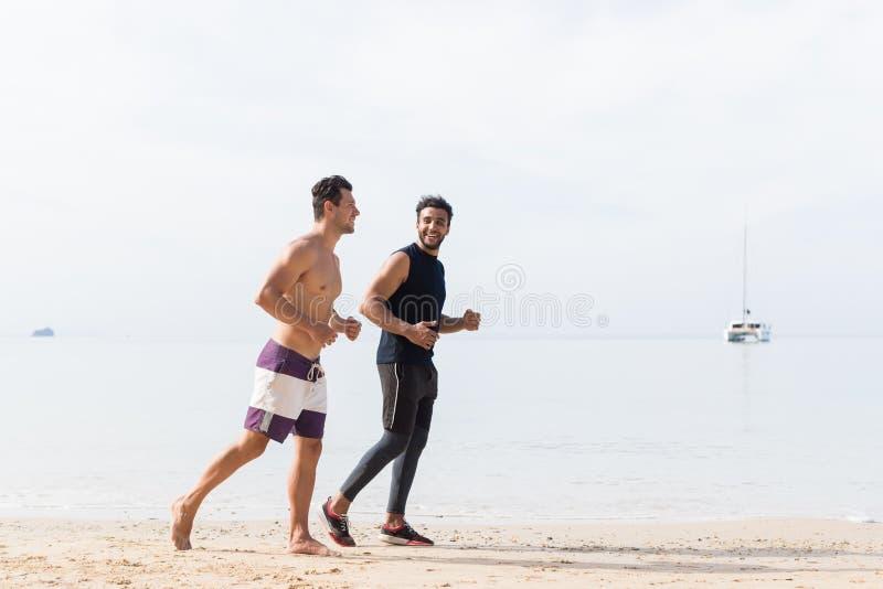 2 люд Jogging на бегунах парней пляжа совместно тренируя на разминке фитнеса спорта взморья Outdoors стоковое изображение