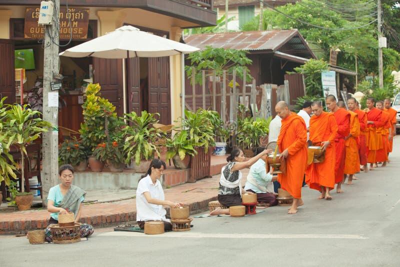 Люди давая милостыни к буддийским монахам на улице, Лаосе стоковое изображение rf