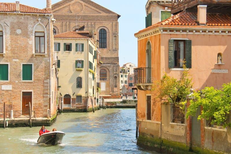 Люди двигают через канал на шлюпку в Венеции, Италии стоковые изображения