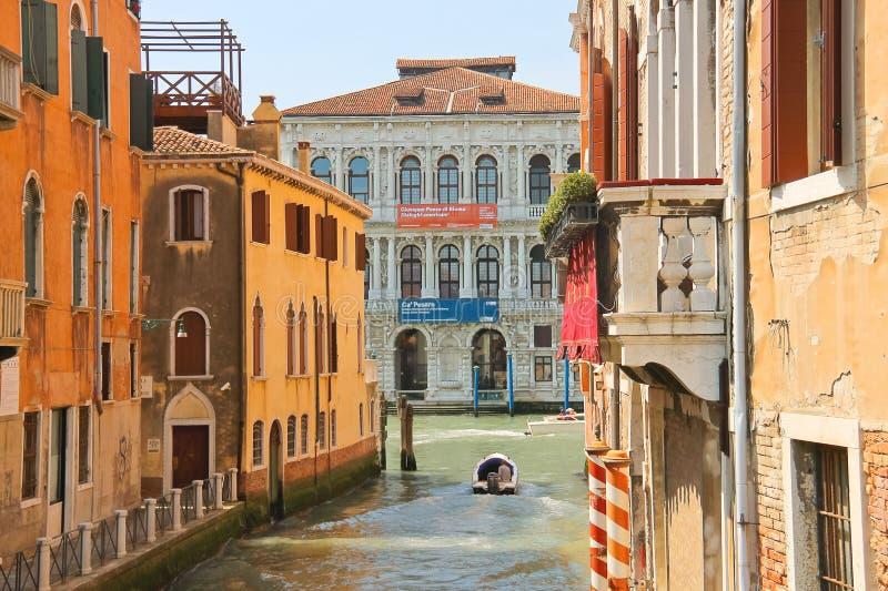 Люди двигают через канал на шлюпку в Венеции, Италии стоковое фото