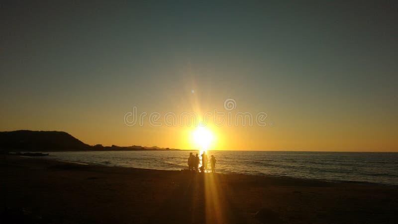 Люди видя заход солнца на пляже стоковые фото
