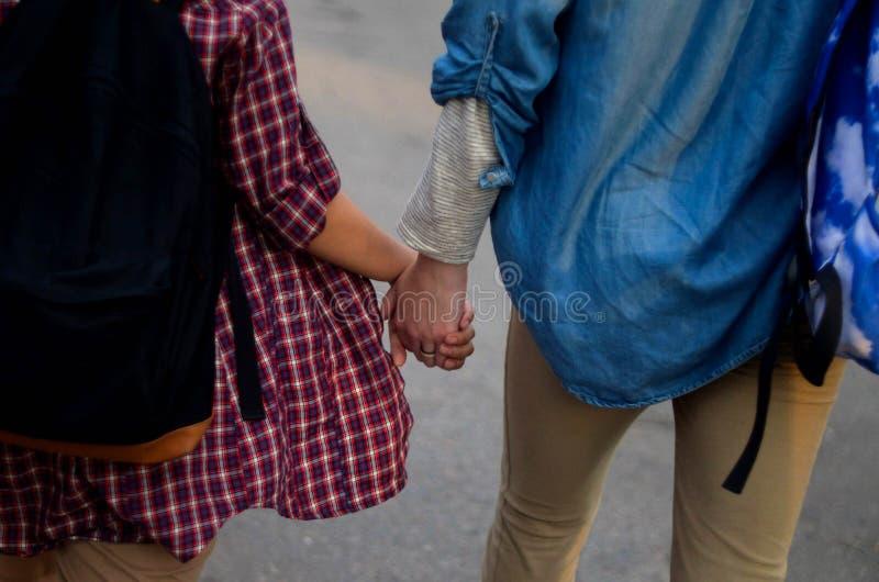 Люди в влюбленности придерживаясь взгляда рук задний стоковая фотография