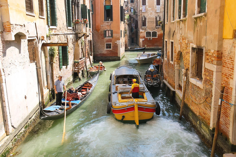 Люди в шлюпках двигают вдоль канала в Венеции, Италии стоковая фотография